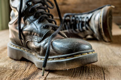 Pair of old boots on wooden floor boards Royalty Free Stock Images