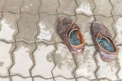 Pair of old brown leather shoes on cement. Stock Images