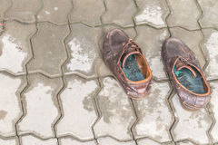 Pair of old brown leather shoes on cement Royalty Free Stock Photos