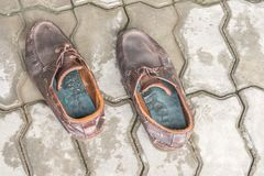 Pair of old brown leather shoes on cement floor. Background Royalty Free Stock Photography