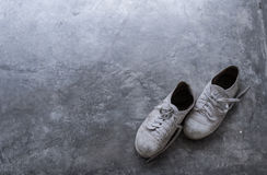 A pair of old dirty shoes on the cement floor with light shading from the corner. Stock Images