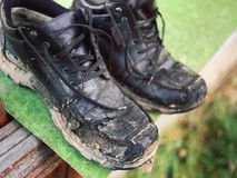 Pair of old dirty shoes. A pair of old dirty shoes drying outdoor after getting wet, outside closeup royalty free stock image