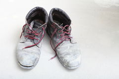 Pair of old dirty work boots in building site Royalty Free Stock Image