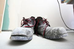 Pair of old dirty work boots in building site Stock Photos