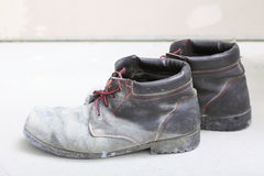 Pair of old dirty work boots in building site Royalty Free Stock Photo