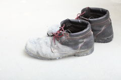 Pair of old dirty work boots in building site Stock Photo