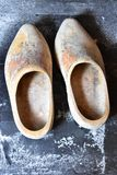 Old wooden dutch shoes on the floor. Pair of old discolored dutch shoes on wooden old floor Stock Image