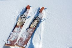 Pair of old fashioned wooden red skis on white snow. Sport equipment royalty free stock image