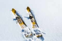 Pair of old fashioned wooden yellow skis on white snow royalty free stock image
