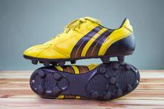 Old yellow football shoes placed on a wooden board, gray background Soft light stock image