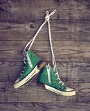 Pair of old green textile sneakers hang from laces. On a gray wooden wall, copy space royalty free stock image