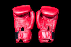 A pair of old red boxing gloves on a black background. Royalty Free Stock Images