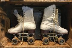 A pair of old, retro, lace-up roller skates stand insdie a wooden box stock photos