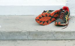 A pair of old running shoes. On steps Stock Photos