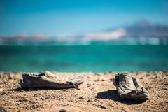 Pair of old shabby shoes on the sandy beach. Old shabby shoes on the sand. Royalty Free Stock Photography