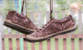 Pair of old sneakers. A pair of old sneakers hanging from the shoelaces stock photos