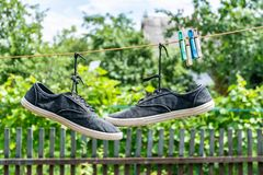 Pair of old sneakers. A pair of old sneakers hanging from the shoelaces royalty free stock photography