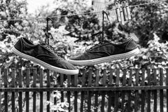 Pair of old sneakers. A pair of old sneakers hanging from the shoelaces royalty free stock photos