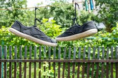 Pair of old sneakers. A pair of old sneakers hanging from the shoelaces royalty free stock photo