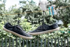 Pair of old sneakers. A pair of old sneakers hanging from the shoelaces stock image