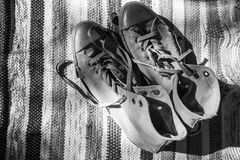 Pair of old sneakers standing on old carpet Stock Images