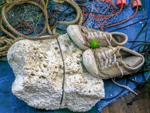 Pair of old sneakers on white foam with fishnet and red rope on the fishing boat. royalty free stock photography
