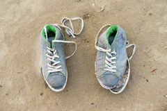 Pair of old sports gym shoes on a sand Stock Image