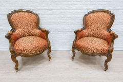 Pair of old vintage luxury armchairs. Pair of old vintage luxury armchairs on the white wall background royalty free stock photos