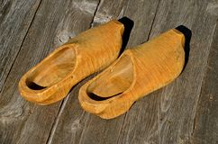 Pair of old Wood Dutch Shoes. A beautiful carved pair of old wood Dutch shoes set on a weathered wood floor Stock Photography