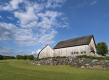 Pair of Old Wooden Barns. Timber frame barns weathered white in color sitting on a bluff with a blue sky and white clouds in New York's Hudson Valley Stock Photos