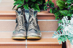 Pair of old worn boots at doorstep. Pair of old worn out boots at doorstep with plants in background Royalty Free Stock Image
