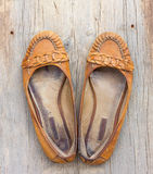 A pair of old worn orange female shoes made of genuine leather on old gray wooden board. With cracks Royalty Free Stock Images