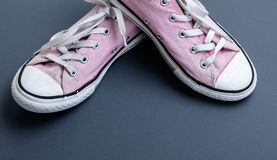 Pair of old worn pink sneakers. With white laces on a black background, close up stock image