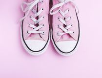 Pair of old worn pink sneakers with white laces stock images