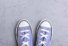 Pair of old worn purple sneakers with white laces. On a gray background, top view stock photos