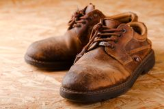 Pair of old worn shoes on wooden boad Royalty Free Stock Photos