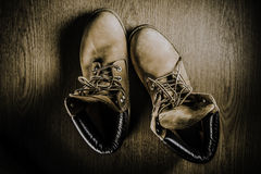 Pair of old yellow working boots Isolated on wood background Royalty Free Stock Images