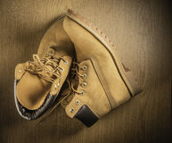Pair of old yellow working boots Isolated on wood background Stock Photo