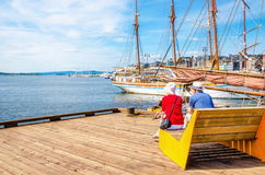 Pair of older people sitting on bench, Oslo Norway. Romantic view of a pair of older people sitting on a bench on the pier and gazing at the sea, Oslo Fjord Stock Photos