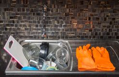 A pair of orange dish washing gloves hangs on a sink faucet surr. Sink full of dirty dishes, cups and glasses Stock Photography