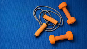 Pair of orange dumbbells and jumping rope on blue yoga mat background Stock Images