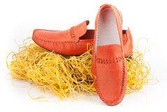 Pair of orange male shoes. Pair of fashion male orange shoes with haystack isolated over white Royalty Free Stock Image