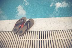 Pair of slippers beside the swimming pool stock image