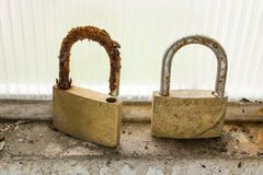 Corrosion. A pair of padlocks that were abandoned in the frame of a garage window suffered the onslaught of corrosion Royalty Free Stock Image