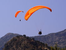 Pair of  Paragliders. Two orange paraglider flying against a blue sky background over mountain tops Stock Image