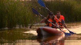 Pair of people in kayaks floats on a river in a sunset. Slow motion stock video