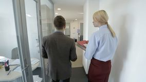A pair pf colleagues are going throught the office and talking. Male and female managers are walking in the corridor with glass walls and coming to big stock footage
