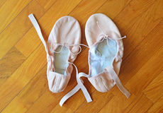 A pair of pink ballet shoes on parquet flooring Royalty Free Stock Photo
