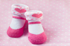 Pair of pink child socks closeup. On spotted pink background, selective focus stock photo