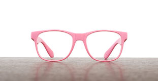Pair of pink eyeglasses on table Royalty Free Stock Photos